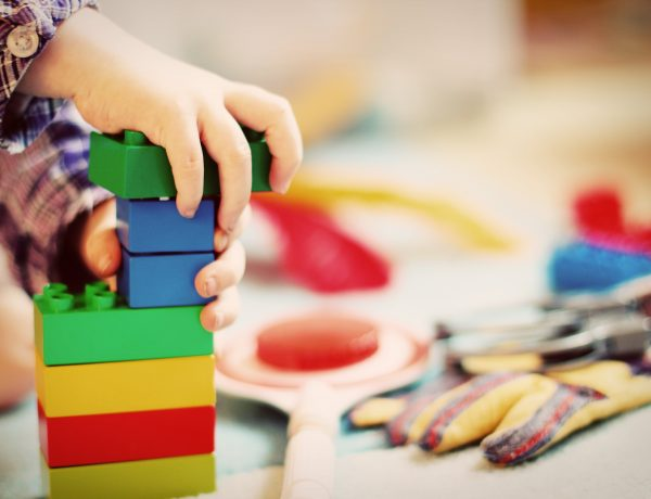 Child playing with blocks to illustrate why to join a toy library even if you have too many toys already